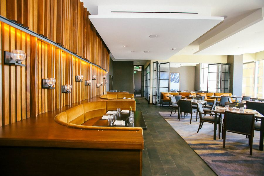 Restaurant dining acrea with acoustical ceiling and wood walls, with custom lighting